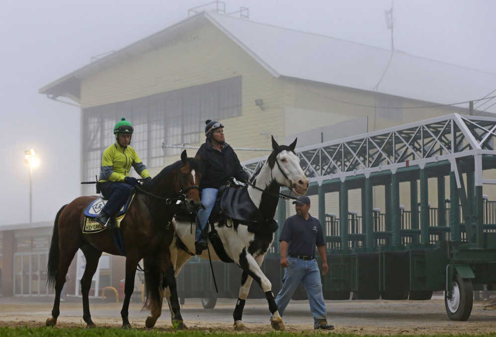 Kid Cruz, left, with exercise rider Reul Munoz aboard, walks past the grandstand after a workout under a thick layer of fog at Pimlico Race Course in Baltimore, Thursday, May 15, 2014. The Preakness Stakes horse race is scheduled to take place May 17.