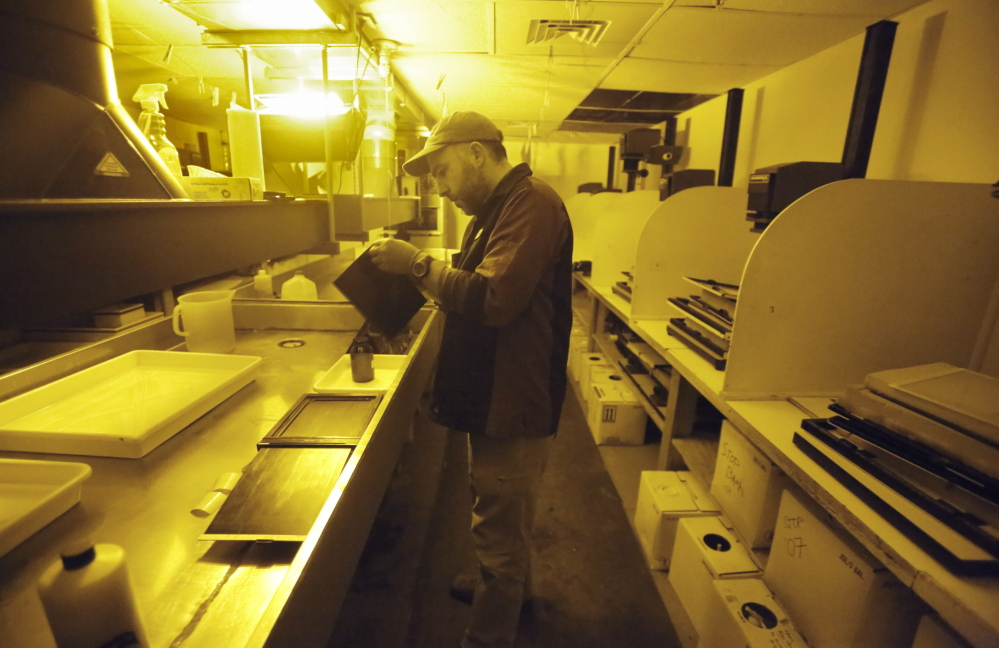 In the darkroom at Maine Media Workshops in Rockport, teaching assistant Mark Dawson prepares the surface of a piece of aluminum that will be used to make a tintype photograph. The school is seeing a surge in interest in its historical processes class and will move its darkroom into a new space in June.