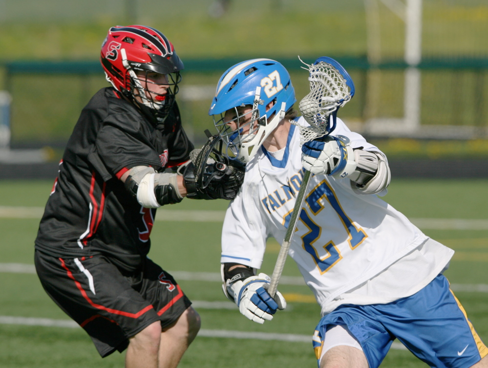Caleb Delisle, left, of Scarborough tries to stop Falmouth's Bryce Kuhn as he heads toward the goal Saturday during a boys' lacrosse game in Scarborough. Falmouth won, 15-11.