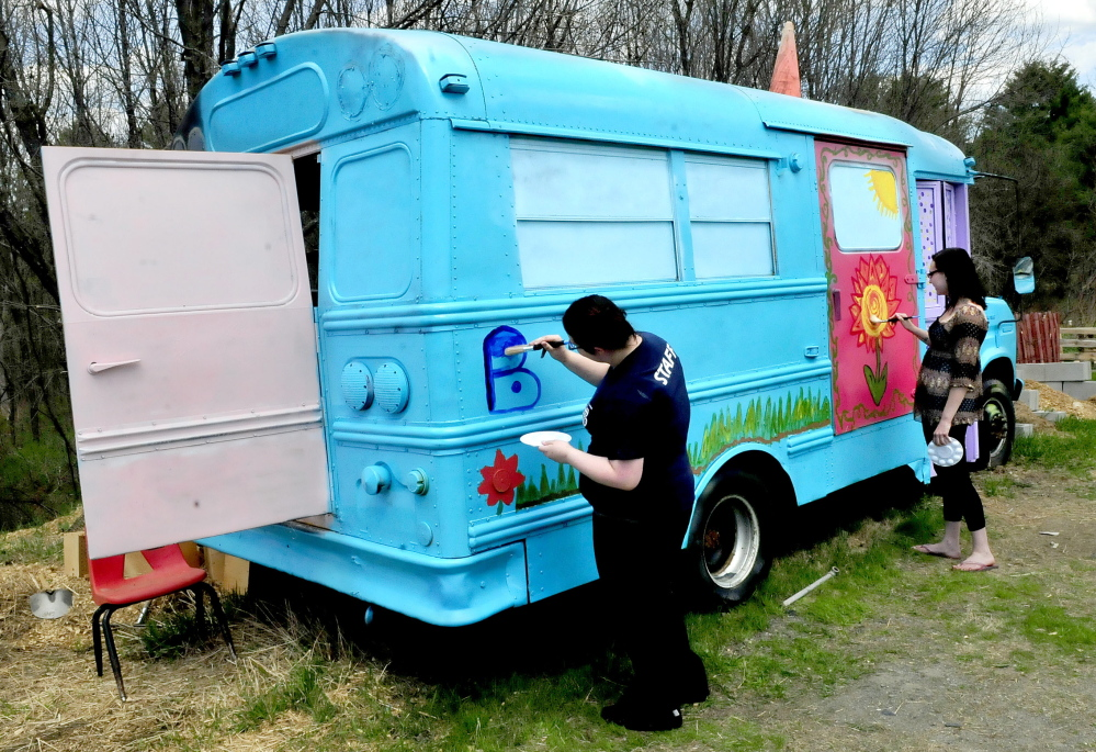 """Sustainable agriculture program students Jade Oliver, left, and Savannah Witham decorate the """"Bunny Bus"""" at the Marti Stevens Learning Center in Skowhegan."""