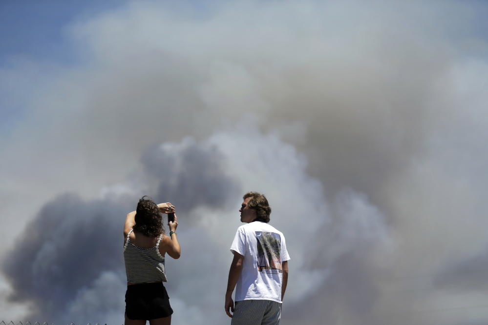 Chase and Brittany Boslet take pictures Friday of smoke from the Las Pulgas fire burning at Camp Pendleton near Oceanside, Calif.