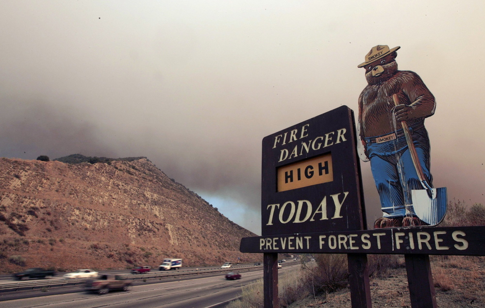 Smoke from a brush fire burning in California's Los Padres National Forest drifts over Interstate 5 near an old Smokey Bear sign. Smokey turns 70 this summer. But instead of kicking back in retirement, the bear in bluejeans is returning to work to educate people about wildfires. Top and below, images of the new Smokey Bear from the Ad Council campaign being rolled out this month.
