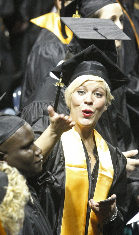 Jennifer Federico of Buxton blows a kiss to a friend as Southern Maine Community College graduates enter the Cumberland County Civic Center in Portland on Sunday for the school's 67th graduation ceremony.