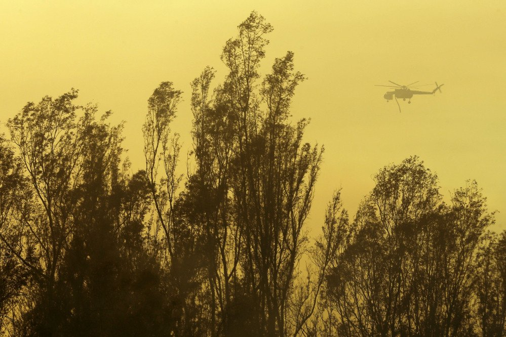 A helicopter transporting water flies over trees during a wildfire Thursday in Escondido, Calif.