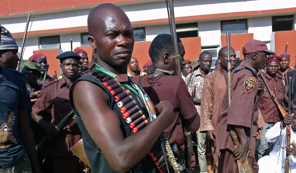 Armed traditional hunters gather in Maiduguri, Nigeria, on Sunday. Hundreds of hunters armed with homemade rifles, poisoned arrows and amulets say their spiritual powers and local knowledge can lead them to the nearly 300 schoolgirls abducted by Islamic extremists.