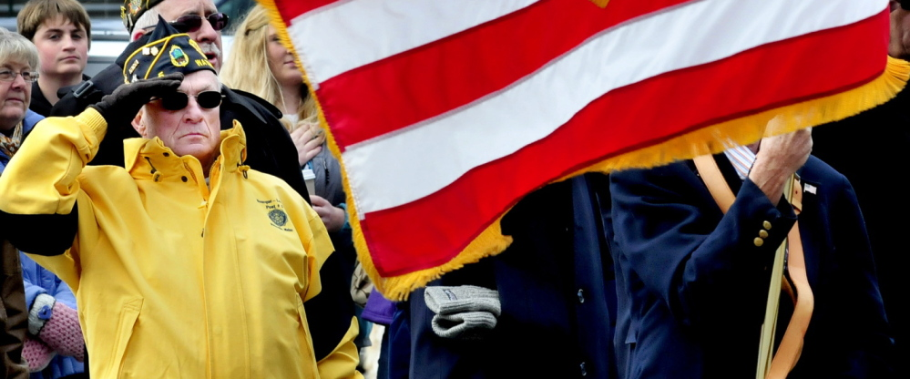 Veteran Reginald Joler salutes during a Veterans Day service following a parade in Waterville on Nov. 11. As more veterans have sought care from the Veterans Affairs health care system, delays have become the norm.
