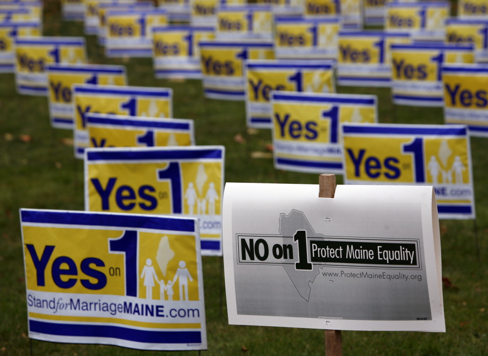 """Posters urging Mainers to vote for a campaign to repeal Maine's same-sex marriage law are seen in Portland in 2009, along with a """"No on 1"""" campaign poster. Maine's ethics panel should follow investigators' recommendations and require the nonprofit that was the chief organizer of """"Yes on 1"""" to register with the state and identify major funders."""