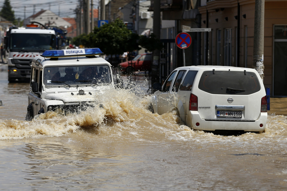 Serbian, left, and Montenegro police cars drive through a flooded street in Obrenovac, 18 miles southwest of Belgrade, Serbia, on Tuesday.