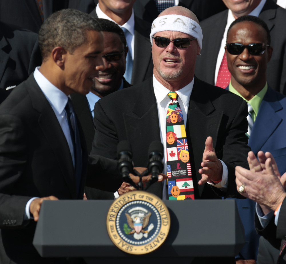 President Barack Obama, left, looks toward quarterback Jim McMahon, wearing headband, as he honors the 1985 Super Bowl XX Champion Chicago Bears football team at the White House in this 2011 photo. McMahon is among eight named plaintiffs in a lawsuit that claims the NFL illegally supplied them with risky painkillers that numbed their injuries and led to medical complications.