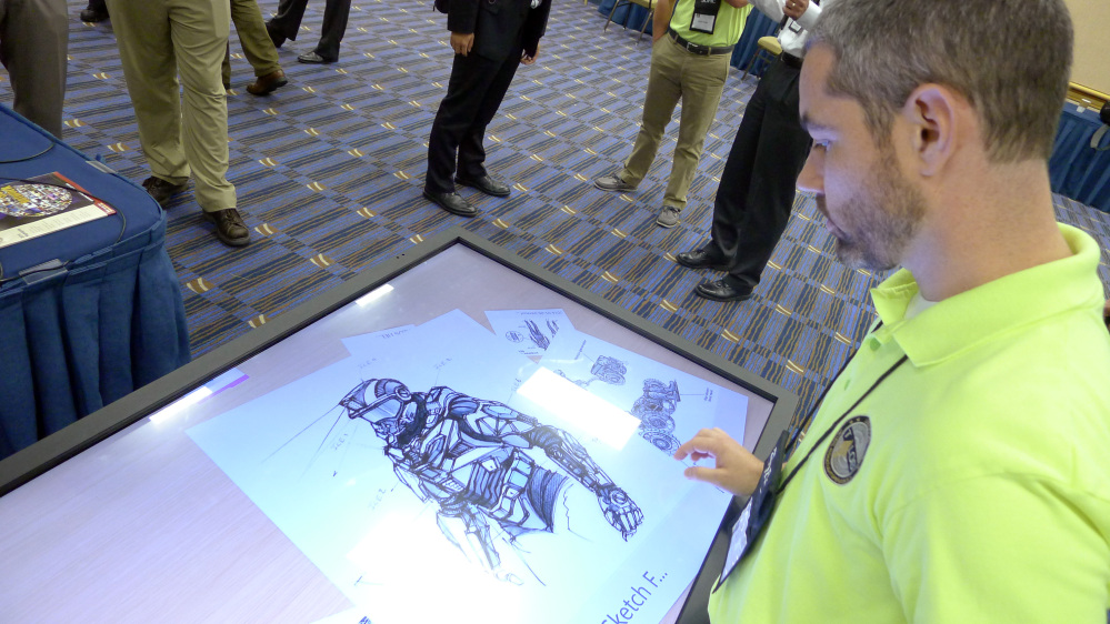 Michael Fieldson, the civilian project manager for the Tactical Assault Light Operator Suit at McDill Air Force Base, looks at sketches of the body armor exoskeleton during the Special Operations Forces Industry Conference in Tampa, Fla., on Monday.