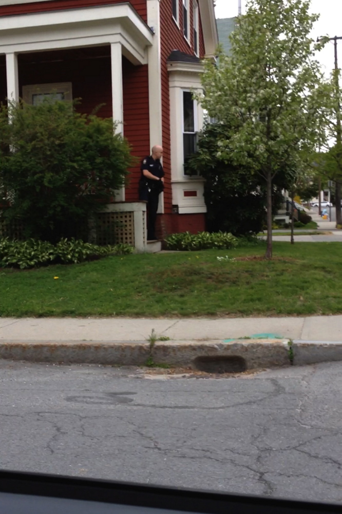 An armed Portland police officers hides behind a home on Revere Street during a tense encounter with a gunman Thursday.
