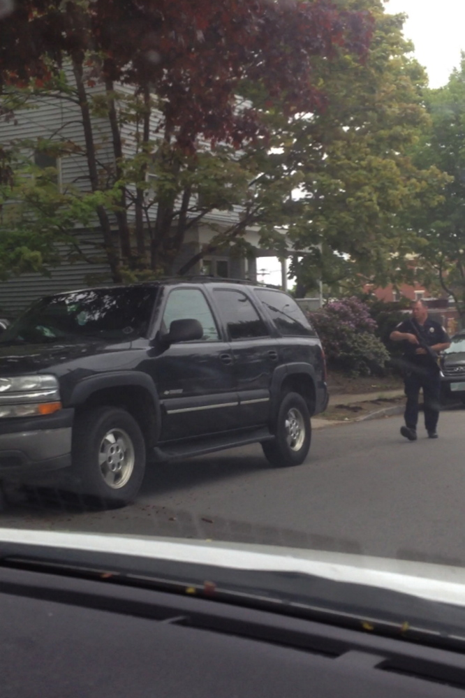 A Portland police officers walks down Revere Street during a tense encounter with a gunman Thursday.
