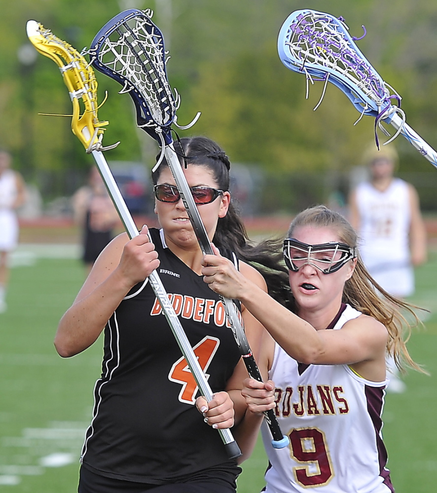 Katherine Dumoulin of Biddeford, left, is pressured by Carly McKenna of Thornton Academy while trying to move in Thursday during Thornton's 11-2 victory at Saco.