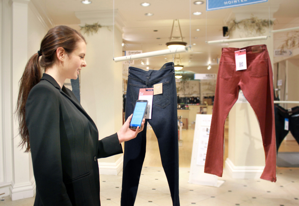 In this photo provided by Hointer, a woman demonstrates the Seattle store's shopping technology. Hointer displays clothing not in piles or on racks but as one piece hanging at a time, like a gallery. Shoppers touch their smartphones to a coded tag on the item and select a color and size. Technology in the store keeps track of the items, and by the time a shopper is ready to try them on, theyíre already at the dressing room.