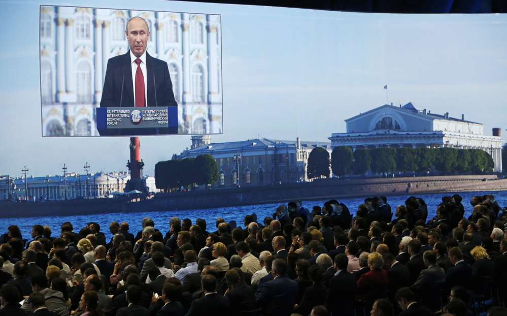 """Participants listen to Russian President Vladimir Putin's address at the St. Petersburg International Economic Forum 2014 in St. Petersburg, Russia, on Friday. Putin said Russia will """"respect the choice of the Ukrainian people"""" in the upcoming vote."""