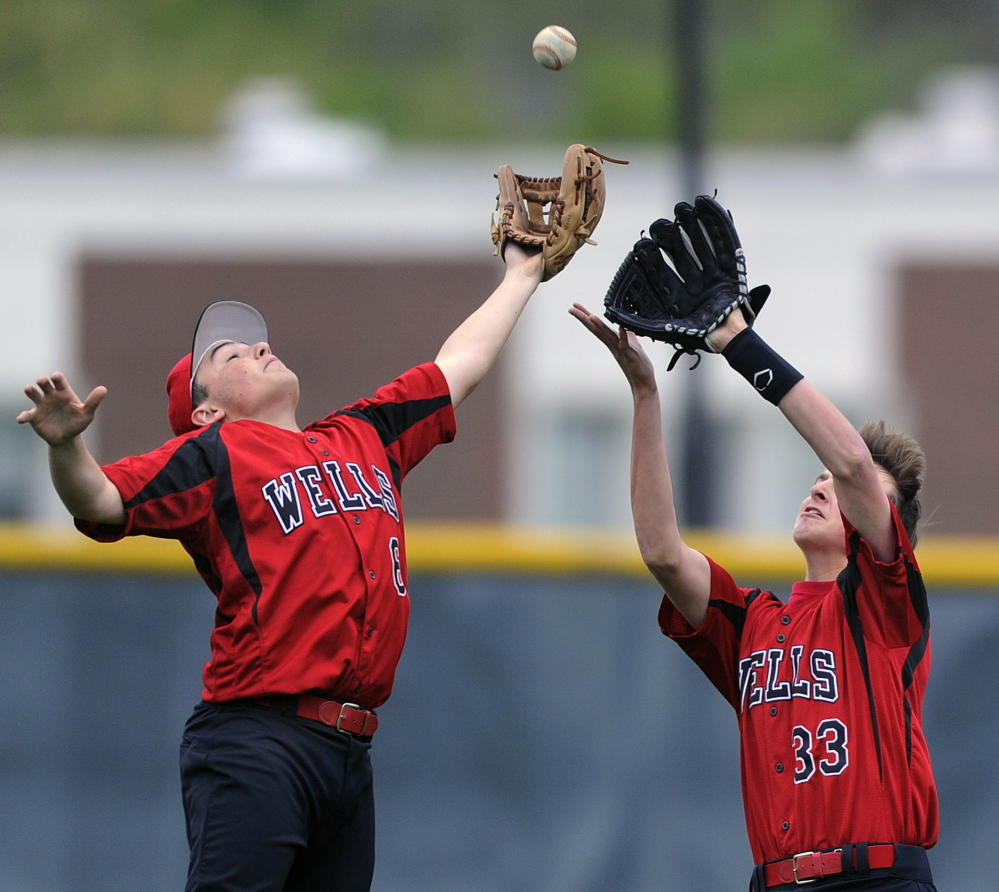 Second baseman Nick Ramsey, left, and right fielder Mick Cousins of Wells converge on a fly ball Friday during a Western Maine Conference game at Cape Elizabeth. Wells tied the game in the sixth inning, then won it 2-1 in the eighth.