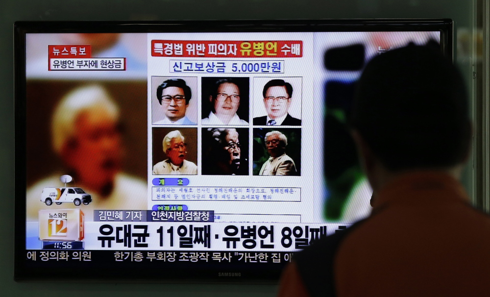 A offer of a reward for information on Yoo Byung-eun appears on a TV news program Friday in Seoul, South Korea. Officials say the billionaire owns a ferry that sank last month.