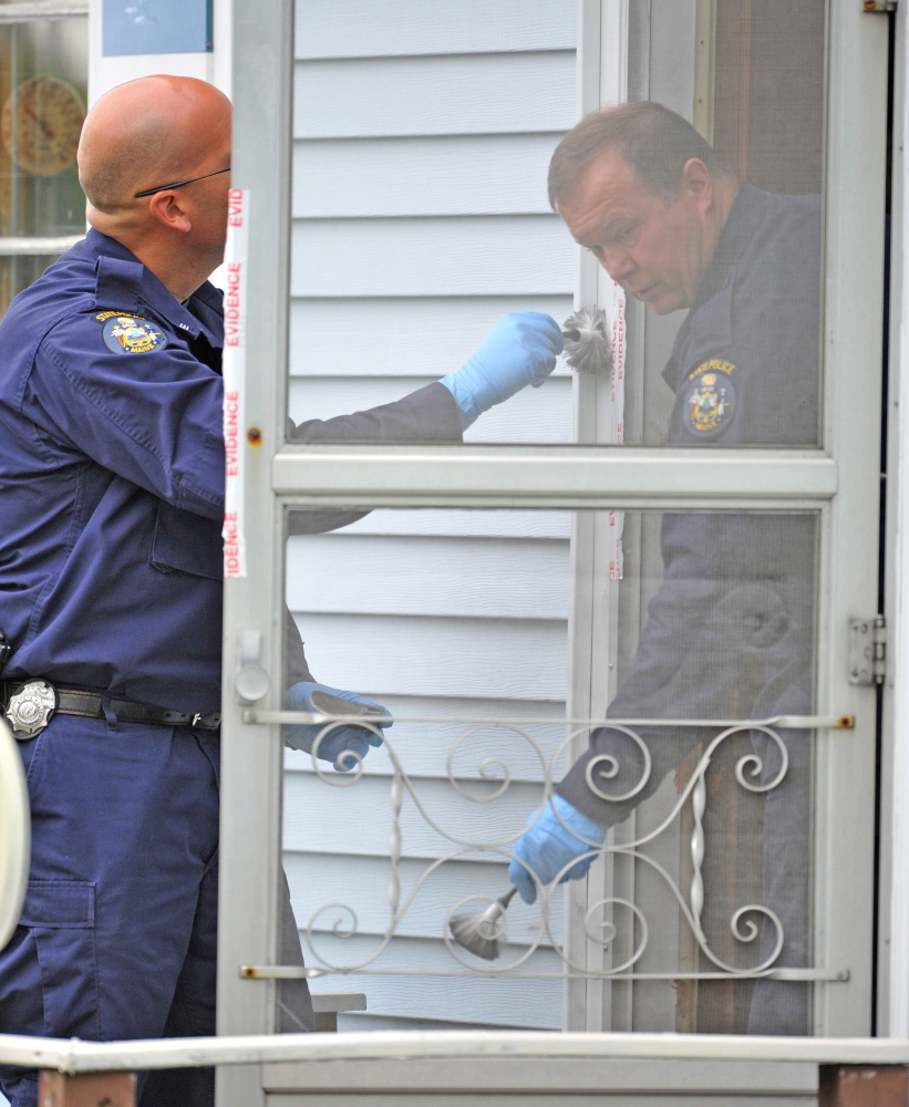 An investigator with the Maine State Police Major Crimes Unit dusts for fingerprints at the residence of Aurele Fecteau, 92, who was found dead in his home on Brooklyn Street in Waterville on Friday.