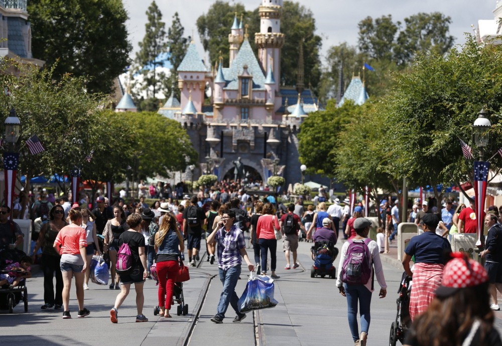 """Patrons walk along Disneyland's Main Street in Anaheim, Calif. Disneyland, which calls itself """"The Happiest Place on Earth,"""" raised its entry prices a week before the Memorial Day weekend that marks the unofficial start of summer."""
