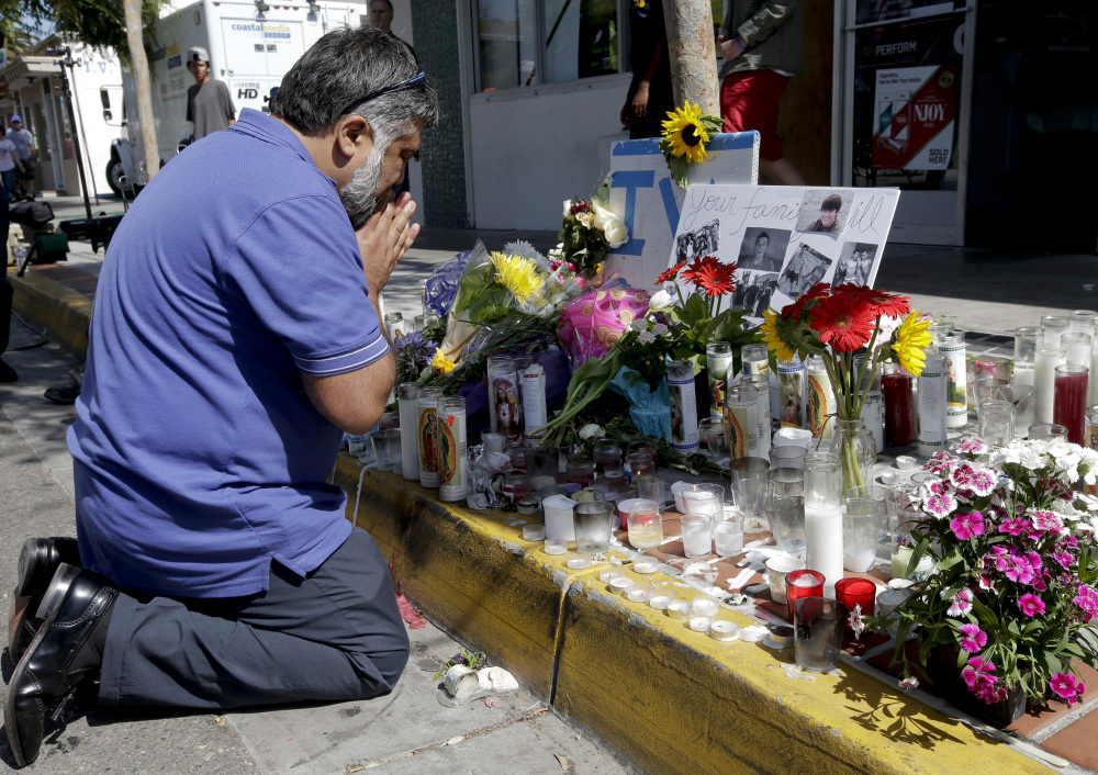 Jose Cardoso pays his respects Sunday at a makeshift memorial in front of the IV Deli Mart, scene of part of Friday night's mass killing in the Isla Vista area near Goleta, Calif. Seven people died in the rampage, including the killer, 22-year-old Elliot Rodger.