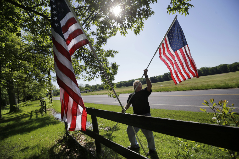 Bob Petersen places flags along a fence for the Memorial Day weekend, at his home in the Cream Ridge section of Upper Freehold, N.J., on Sunday.