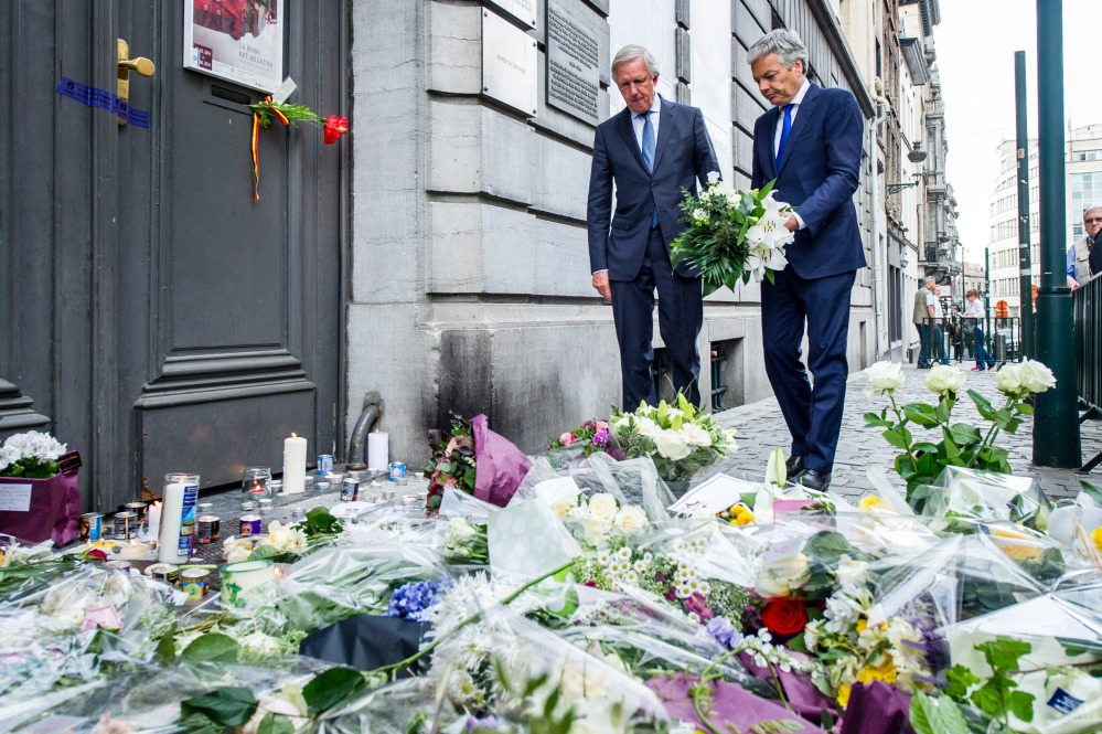 Belgium's Foreign Minister Didier Reynders, right, lays flowers at the Jewish Museum in Brussels on Sunday. Police stepped up security at Jewish institutions, schools and synagogues after four people were killed in a spree of gunfire at the Jewish Museum in Brussels on Saturday.