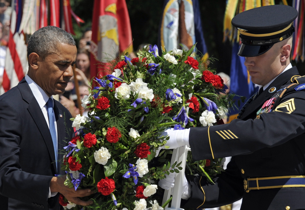 President Obama lays a wreath at the Tomb of the Unknowns at Arlington National Cemetery on Monday, leading the nation in remembering its war heroes.