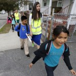Children walk home from school escorted by Allyson Trenteseaux, center right. a Walking School Bus program manager, in Providence, R.I. The program is seen as a way to get kids active, fight childhood obesity and cut absenteeism.
