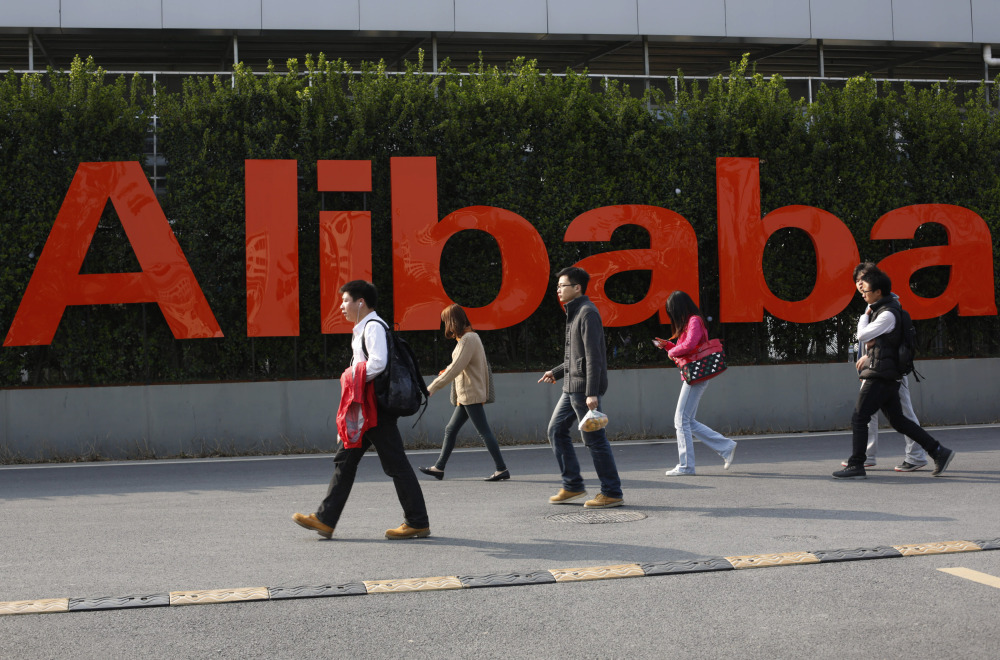 People walk past a company logo at the headquarters of Alibaba Group in Hangzhou, in eastern China's Zhejiang province.
