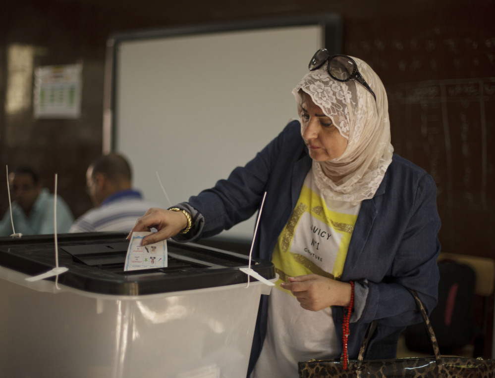 An Egyptian woman casts her vote Tuesday, the second and final day of the presidential election. Low turnout has marked both days of voting,