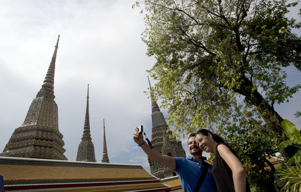 A couple of Western tourists snap a souvenir photo at a Wat Pho temple in Bangkok, Thailand Tuesday.