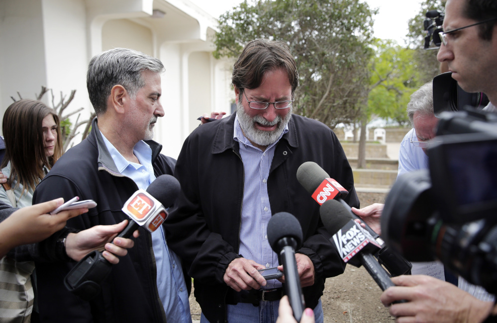 Richard Martinez, center, is comforted by his brother Alan as he talks to media outside the Santa Barbara County Sheriff's Headquarters on Saturday. Martinez is pushing for gun control after his son was killed in a rampage Friday.
