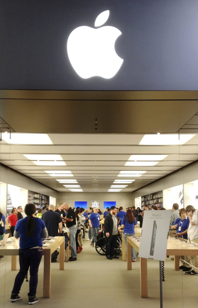 Apple employees, in blue shirts, work with customers at the Apple Store at the Maine Mall in South Portland. 2012 Press Herald file/Gregory Rec
