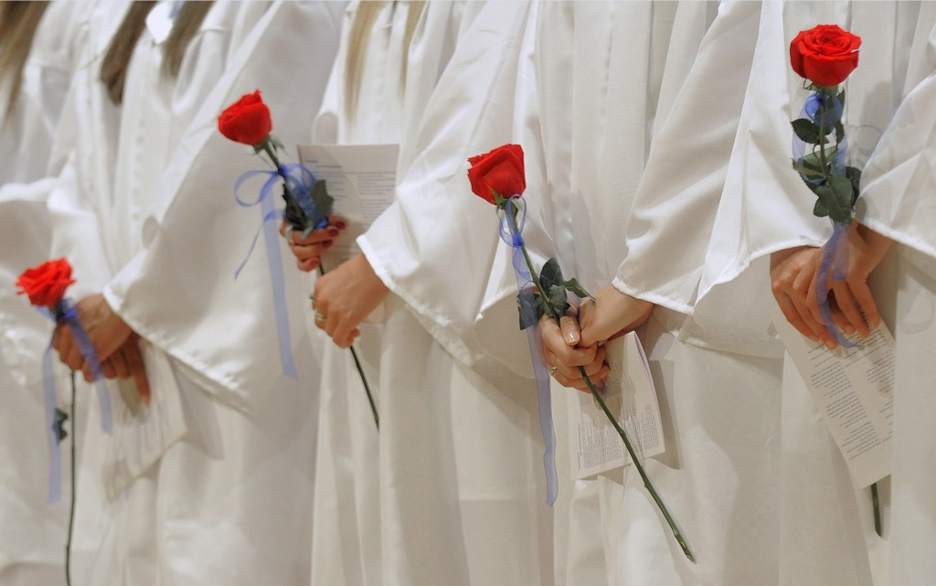 Female members of Portland High School's Class of 2013 hold roses during the graduation ceremony at Merrill Auditorium Thursday, June 6, 2013.