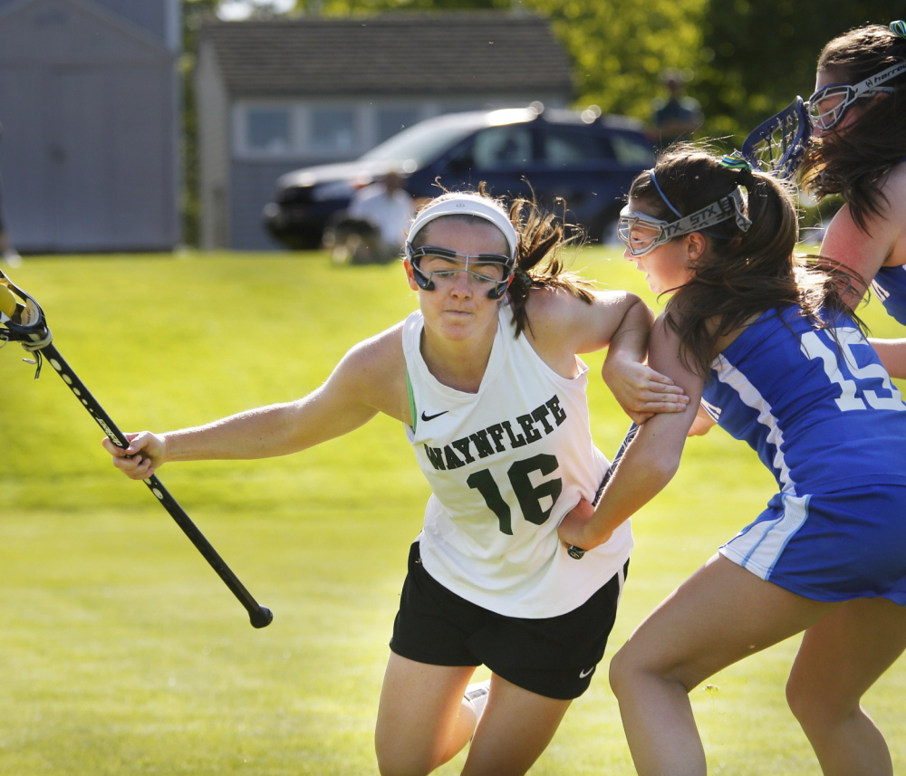 Leigh Fernandez, who scored the game-winning goal in the third overtime for Waynflete, tries to create space Thursday while being defended by Haley Fecko, left, and Kyra Schwartzman of Kennebunk. Waynflete won, 7-6. Photo by Derek Davis/Staff Photographer