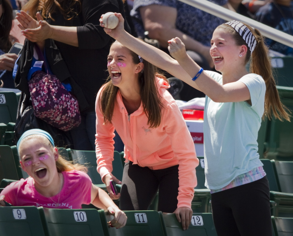 Jane Greenberg, right, celebrates after catching a foul ball during Education Day at the Portland Sea Dogs game at Hadlock Field Thursday. She was joined by friends Sydney Michelson, center, and Mia Kelley,  left. The girls are from Scarborough. Carl D. Walsh/Staff Photographer