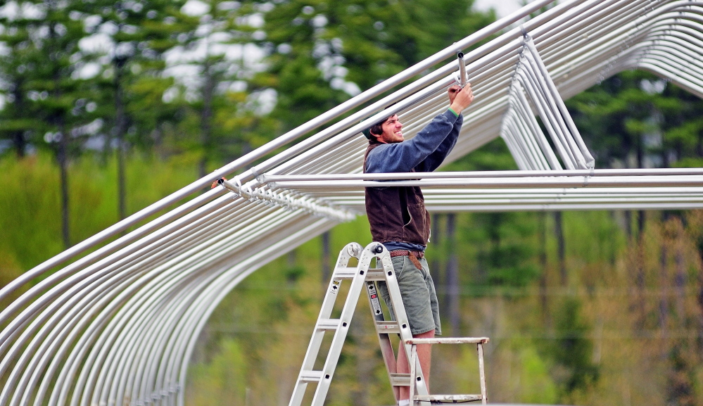 MONMOUTH, ME - MAY 14: Kevin Leavitt, assembles a high tunnel greenhouse on Wednesday May 14, 2014 on a Monmouth horse farm where he rents a field. Leavitt said that he'd use it to grow cucumbers and tomatoes for his CSA clients and customers at farmers markets. (Photo by Joe Phelan/Staff Photographer)