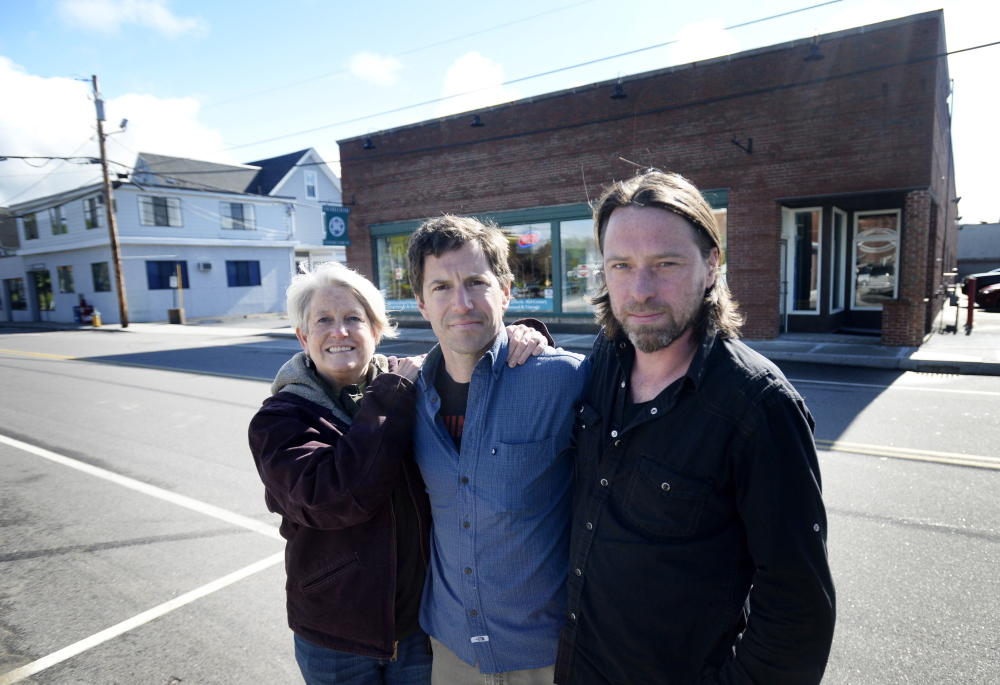 Penny Jordan, left, and Ben Slayton, center, pose with Joe Fournier, who will be the general manager of their new store in South Portland. They plan to sell locally grown and raised produce and meats in the building shown behind them, 161 Ocean St. Their mission is make local foods easily accessible to ordinary families. Shawn Patrick Ouellette/Staff Photographer