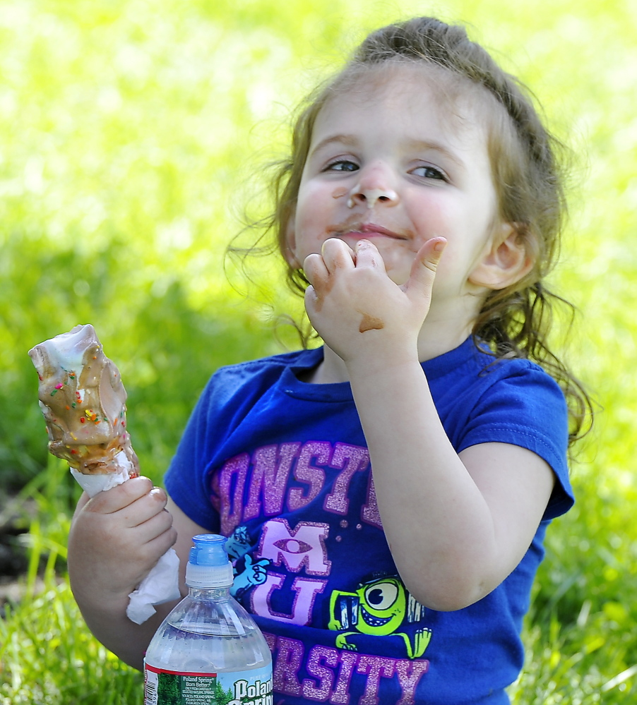 Three-year-old Brook Lowell of Lewiston wipes the  ice cream on her face.