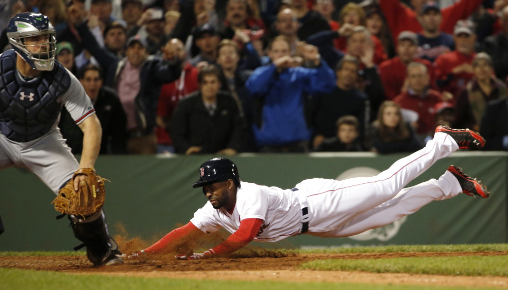 Boston Red Sox's Jackie Bradley Jr. dives home with the game-winning run on an infield single by teammate Xander Bogaerts during the ninth inning of their 4-3 win at Fenway Park on Thursday night.