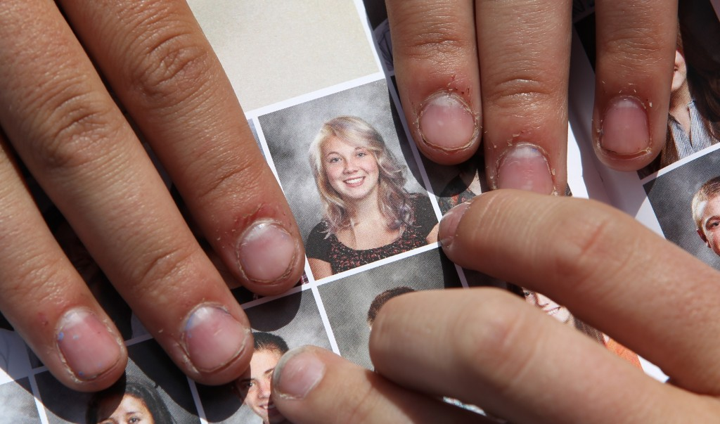 Wasatch High School sophomore Rachel Russell, 16, points to her altered school yearbook photo. Russell had sleeves added to her picture.