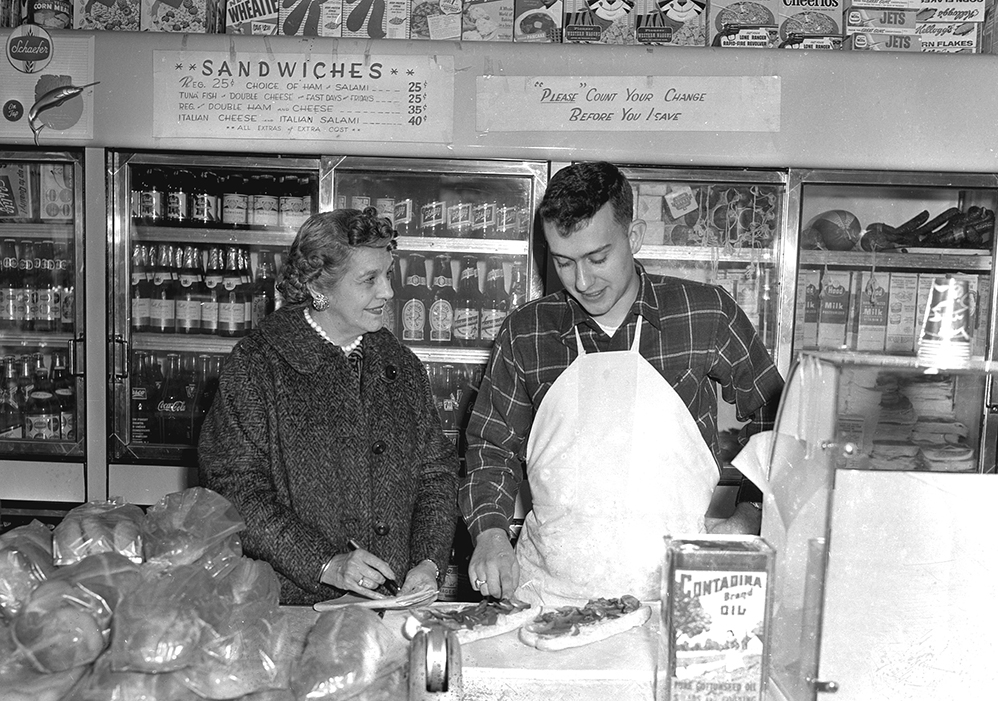 This photo, originally printed on the front page of the April 9, 1959 Portland Press Herald and credited to Staff Photographer Elwell, shows 'Mrs. Donald C. Bailey' (following the convention of the time, her own first name is not given), an agent of the Greater Portland Chamber of Commerce, with John F. Amato at Amato's sandwich shop on India Street in Portland.