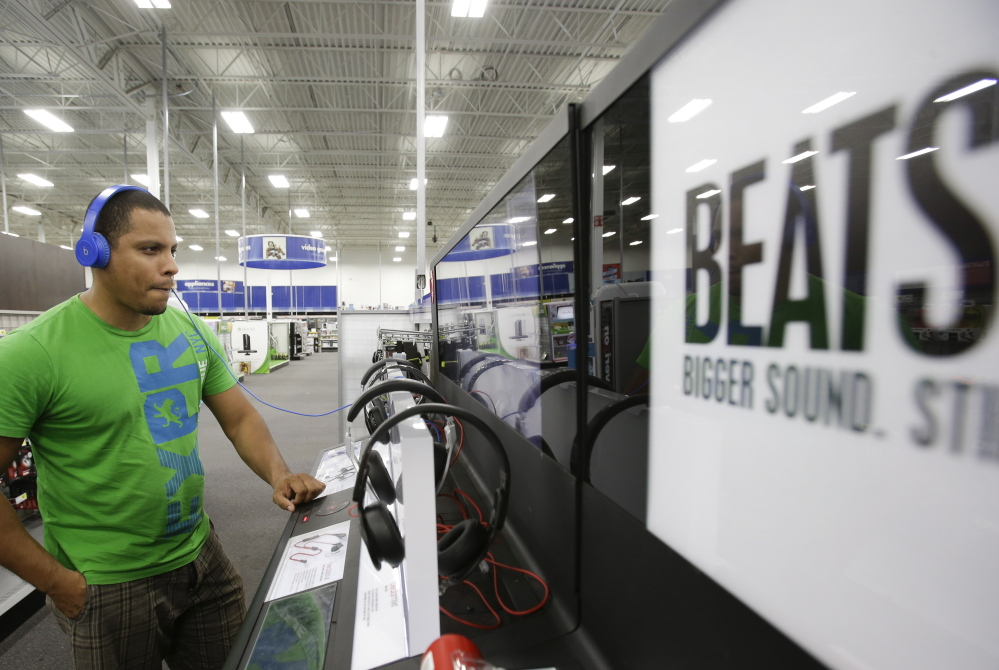 Eric Soriano listens tries a pair of Beats headphones at a Best Buy in Orlando, Fla. Apple's lure to buy Beats, however, had more to do with the company's streaming music service as Apple looks to broaden its appeal in both music and hardware. The Associated Press