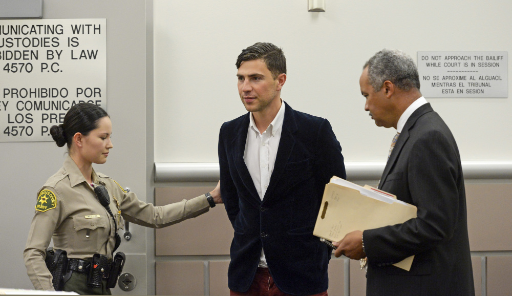 Vitalii Sediuk, from Ukraine, is led into the courtroom with his attorney Anthony Willoughby, right in Los Angeles Superior Court  Friday, May 30, 2014, in Los Angeles. Sediuk faces four misdemeanor charges in connection with an alleged May 28 attack on actor Brad Pitt at a Los Angeles movie premiere. The Associated Press