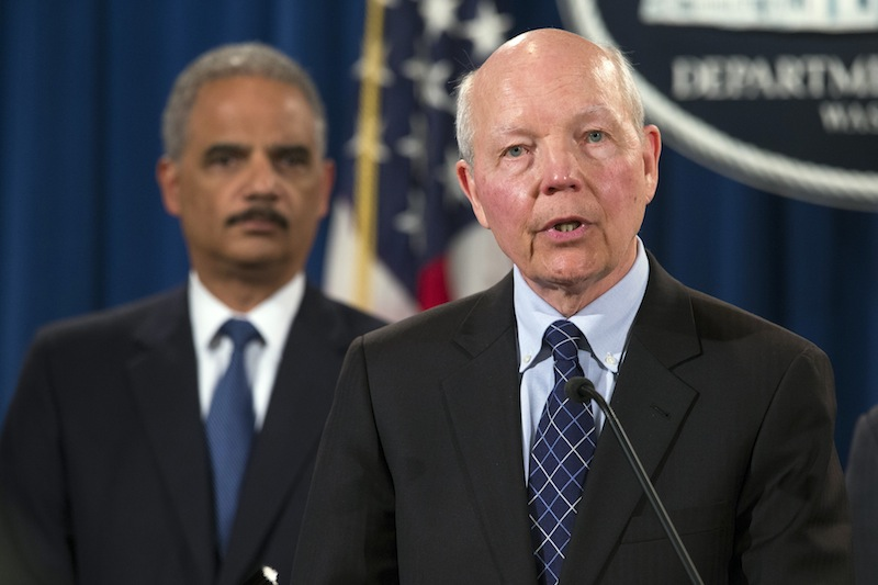 Attorney General Eric Holder, left, listens as IRS Commissioner John Koskinen speaks during a news conference at the Justice Department on Monday in Washington. The Justice Department charged Credit Suisse AG with helping wealthy Americans avoid paying taxes through offshore accounts.