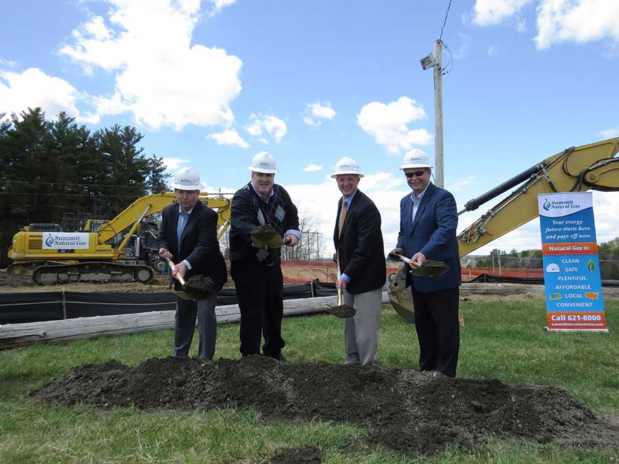 From left to right: Mike Minkos, president, Summit Natural Gas of Maine; Steve Woods, chairman, Yarmouth Town Council; Nathan Poore, town manager, Falmouth; and Bill Shane, town manager, Cumberland, all dig in the dirt at the groundbreaking ceremony at the Cumberland Fairgrounds.