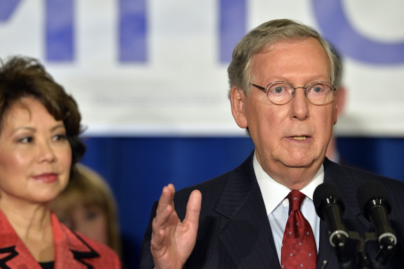 With his wife, Elaine Chao, looking on, Kentucky Sen. Mitch McConnell addresses his supporters following his victory in the Republican primary Tuesday at the Marriott Louisville East in Louisville, Ky.