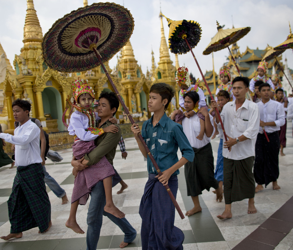 Buddhist men carry their sons and nephews at the Shwedagon pagoda in Yangon, Myanmar, in April. The government views a religious conversion bill as politically sensitive. The Associated Press