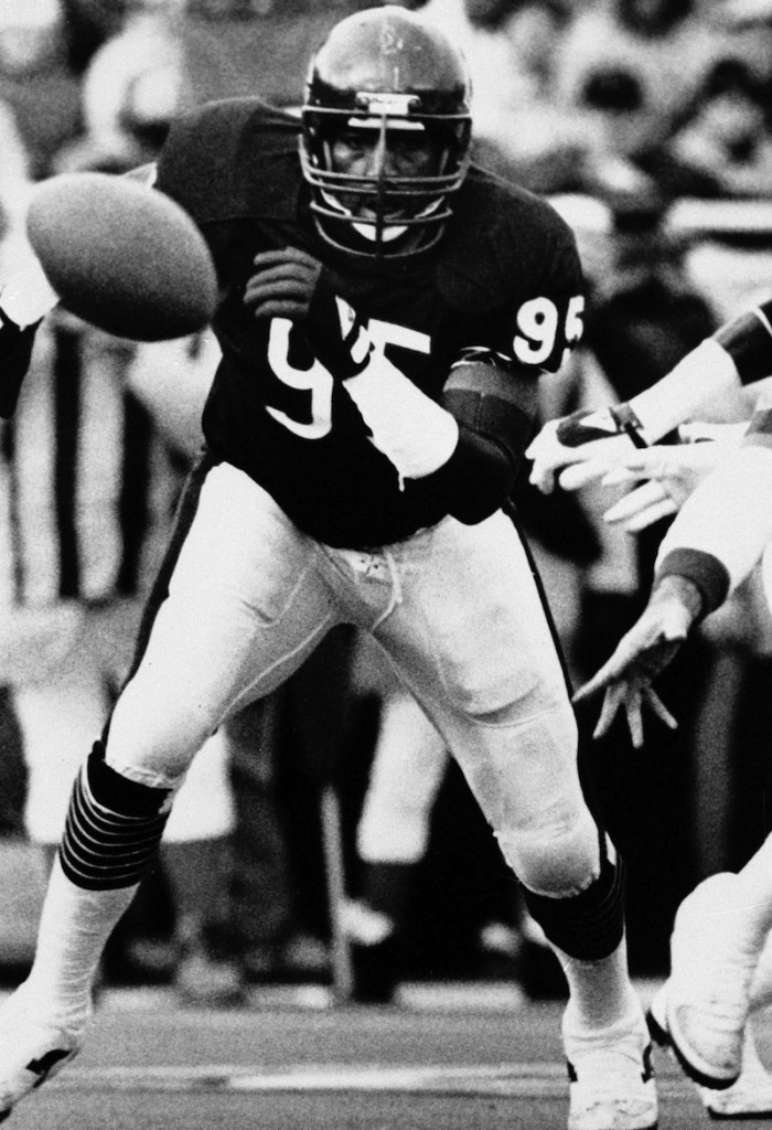 This January 1986 file photo shows Chicago Bears defensive end Richard Dent chases a loose ball during the NFL playoffs in Chicago. A group of retired NFL players says in a lawsuit filed Tuesday that the league, thirsty for profits, illegally supplied them with risky narcotics and other painkillers that numbed their injuries for games and led to medical complications down the road.