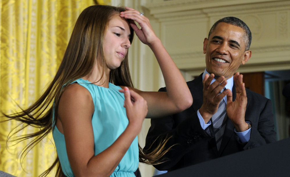 President Barack Obama applauds Victoria Bellucci, a 2014 graduate of Huntingtown High School in Huntingtown, Md., at a White House youth sports concussion summit Thursday. Bellucci suffered five concussions while playing high school and club soccer. The Associated Press